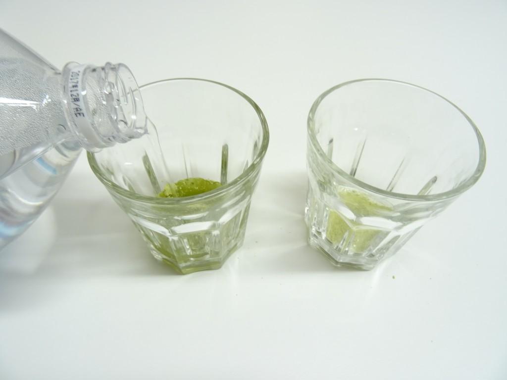 ゴーヤ粉末が入ったコップに水を灌ぐ